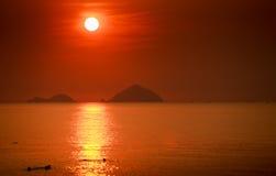 de mensensilhouetten zwemmen in overzees tegen zon in rode hemel bij zonsopgang Royalty-vrije Stock Afbeelding