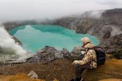 De mensentoerist bekijkt het zwavelmeer op de Ijen-vulkaan op het eiland Java in Indonesi? Wandelaarmens met rugzak stock foto's