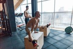 De mensentraining van de handstandopdrukoefening bij gymnastieketters UPS Stock Foto