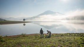 De mensentribune door meer anh alleen boom op het meer, zonsopgang bij mistige mountai, wolk op de hemel Royalty-vrije Stock Afbeeldingen