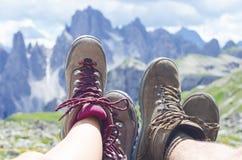 De mensenwandelaar ligt op een grond Pieken zoals een achtergrond Zonnige dag Trekkingslaarzen Abstracte verlichtingsachtergronde Stock Afbeelding
