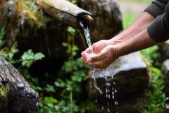 De mensenwas dient vers, koud, drinkbaar water in stock afbeeldingen