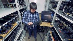 De mensenwerken in een centrum van de cryptocurrencymijnbouw stock video