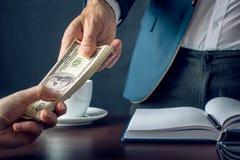 De mensenzakenman in kostuum neemt de geldhanden Een steekpenning in de vorm van dollarrekeningen Concept corruptie en omkoperij royalty-vrije stock foto