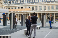 De mensenzitkamer en neemt beelden onder Colonnes DE Buren, Pari Royalty-vrije Stock Foto's