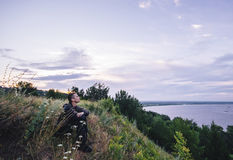 De mensenzitting op de bank van de rivier bij zonsopgang en overweegt mooi landschap Stock Afbeeldingen
