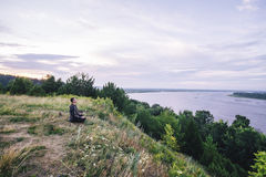 De mensenzitting op de bank van de rivier bij zonsopgang en overweegt mooi landschap Royalty-vrije Stock Foto's