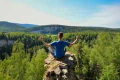 De mensenzitting op de bovenkant van de berg in yoga stelt Stock Foto's