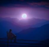 De mensenzitting op een houten omheining en geniet volle maan van het toenemen Royalty-vrije Stock Afbeeldingen