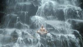 De mensenzitting in yoga stelt bij achtergrondwaterval stock footage