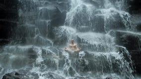 De mensenzitting in yoga stelt bij achtergrondwaterval stock videobeelden