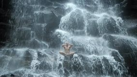 De mensenzitting in yoga stelt bij achtergrondwaterval stock video