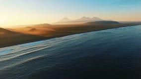 De mest härliga solnedgångarna över havet I avståndsbergen i dimma Filmande från luften stock video