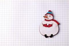 De met de hand gemaakte houten sneeuwman van de Kerstmisdecoratie op geregeld document Royalty-vrije Stock Foto's