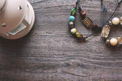 De met de hand gemaakte kleurrijke parels op een zwarte draad liggen op een houten lijst Stock Afbeeldingen