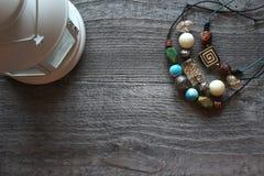 De met de hand gemaakte kleurrijke parels op een zwarte draad liggen op een houten lijst Royalty-vrije Stock Foto