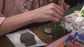 De met de hand gemaakte vaas van de meisjesverf van klei bij lijst door borstel in groene kleur festival verwezenlijking hobby stock video