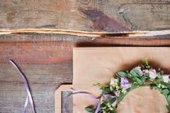 De met de hand gemaakte bloemendietiara van bloemen wordt gemaakt ligt op houten achtergrond Modieuze hand - gemaakte kroon van b stock fotografie