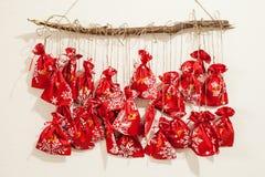 De met de hand gemaakte kalender van de Kerstmiskomst voor kinderen, rode komst genummerd zakken die op muur hangen die op te ope stock foto's