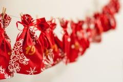 De met de hand gemaakte kalender van de Kerstmiskomst voor kinderen, rode komst genummerd zakken die op muur hangen die op kinder stock foto's