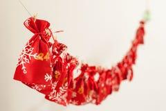 De met de hand gemaakte kalender van de Kerstmiskomst voor kinderen, rode komst genummerd zakken die op muur hangen die op kinder stock foto