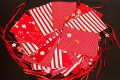 De met de hand gemaakte kalender van de Kerstmiskomst voor kinderen, rode komst genummerd zakken klaar om met speelgoed worden op stock foto