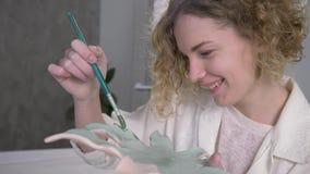 De met de hand gemaakte vaardigheid, het inspireren schildersmeisje maakt het schilderen op kleiaardewerk met borstel bij aardewe stock videobeelden