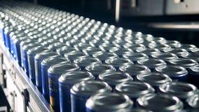 De metaalblikken met bier op een lopende band, sluiten omhoog stock videobeelden