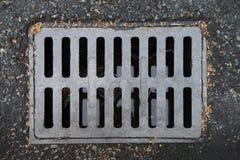 De metaaldekking voor de drainage op de straat stock afbeeldingen