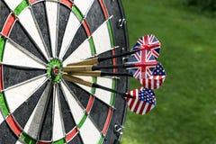 De metaalpijltjes hebben rode bullseye op een dartboard geraakt Het spel van pijltjes De pijltjespijl in de pijltjes van het doel Royalty-vrije Stock Afbeeldingen