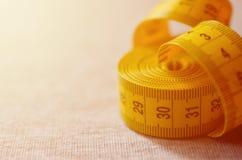 De metende band van gele kleur met numerieke indicatoren in de vorm van centimeters of duim ligt op een grijze gebreide stof Royalty-vrije Stock Afbeelding