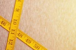 De metende band van gele kleur met numerieke indicatoren in de vorm van centimeters of duim ligt op een grijze gebreide stof Stock Afbeelding