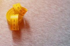 De metende band van gele kleur met numerieke indicatoren in de vorm van centimeters of duim ligt op een grijze gebreide stof Royalty-vrije Stock Foto