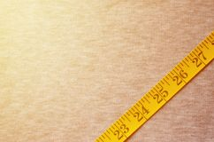 De metende band van gele kleur met numerieke indicatoren in de vorm van centimeters of duim ligt op een grijze gebreide stof Royalty-vrije Stock Foto's
