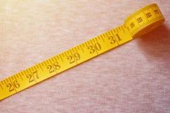 De metende band van gele kleur met numerieke indicatoren in de vorm van centimeters of duim ligt op een grijze gebreide stof Royalty-vrije Stock Fotografie