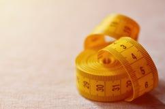 De metende band van gele kleur met numerieke indicatoren in de vorm van centimeters of duim ligt op een grijze gebreide stof Stock Fotografie