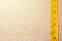De metende band van gele kleur met numerieke indicatoren in de vorm van centimeters of duim ligt op een grijze gebreide stof Stock Foto's