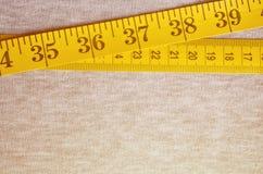 De metende band van gele kleur met numerieke indicatoren in de vorm van centimeters of duim ligt op een grijze gebreide stof Stock Foto