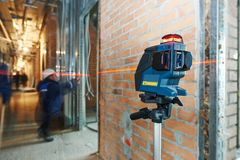 De meting van het laserniveau bij bouwwerf Stock Afbeelding