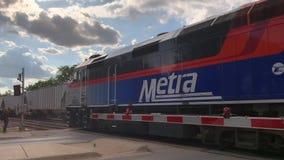 De de Metratrein en goederentrein gaan elkaar bij het station van het Villapark in de voorsteden van Chicago over stock videobeelden