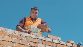 De metselaar bouwt muren overeenkomstig bouwplannen stock footage