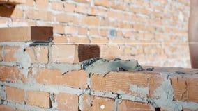 De metselaar bouwt muur in huis stock footage