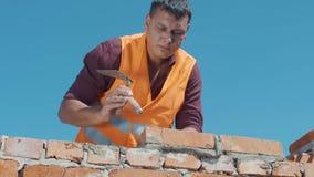 De metselaar bouwt muur op een blauwe hemelachtergrond stock video