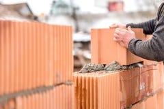 De metselaar die van de metselaararbeider bakstenen muren installeren Stock Afbeelding