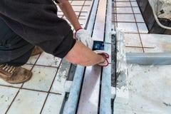 De metselaar installeert een afvoerkanaalgeul op een terras Royalty-vrije Stock Afbeelding