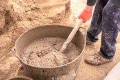 De metselaar kneedt cementmortier voor het gieten van concrete screed royalty-vrije stock fotografie