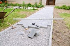 De metselaar plaatst concrete straatsteenblokken voor het opbouwen van een terras, gebruikend hamer en waterpas Stock Foto's