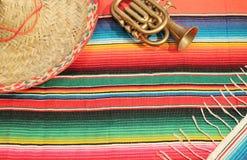 De Mexicaanse deken van de fiestaponcho in heldere kleuren met sombrero Stock Afbeeldingen
