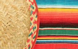 De Mexicaanse deken van de fiestaponcho in heldere kleuren met sombrero Stock Afbeelding