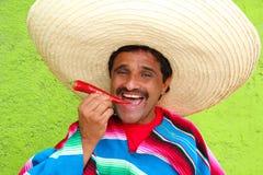 De Mexicaanse sombrero die van de mensenponcho roodgloeiende Spaanse peper eet Stock Fotografie